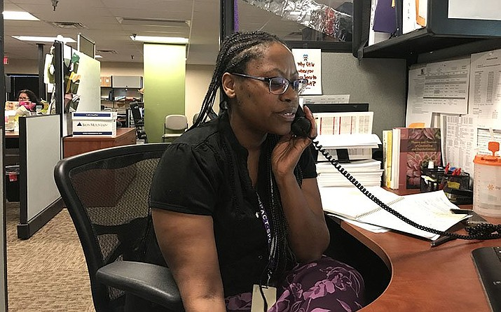 Lisa Clark, a clinical coordinator at Empact Suicide Prevention Center, talks to a caller who is discouraged about problems in his life. (File photo by Shawna Truong/Cronkite News)
