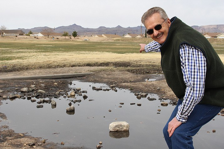 Former Mohave County Development Services Director Nick Hont points to the Monsoon Park basin that can be used to capture runoff from the mountains after rains. (Daily Miner File Photo)