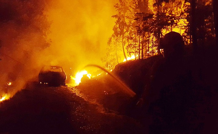 Firefighters spray down a burning propane tank and car in the Treehouse Fire, south of Walker Friday night, June 8, 2018. (Walker Fire Department/Courtesy)