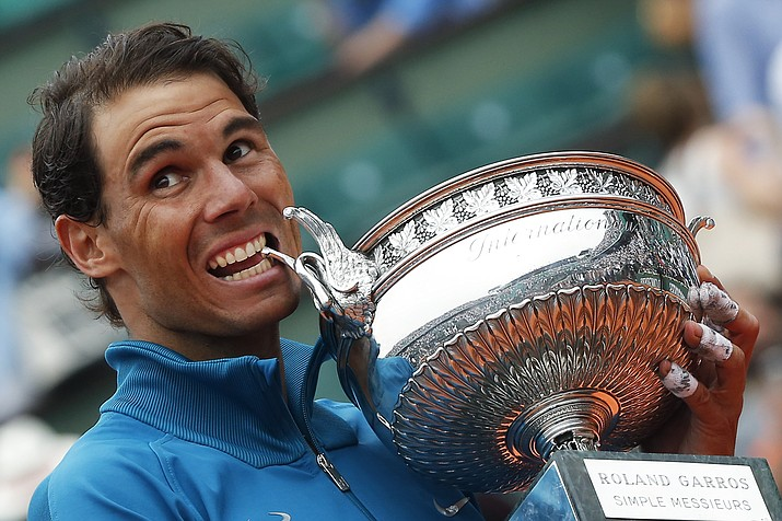 Eleven-time French Open winner Spain's Rafael Nadal bites the trophy as he celebrates after the men's final match of the French Open tennis tournament against Austria's Dominic, Thiem who was beaten in three sets 6-4, 6-3, 6-2, at the Roland Garros stadium in Paris, France, Sunday, June 10, 2018. (Michel Euler/AP Photo)