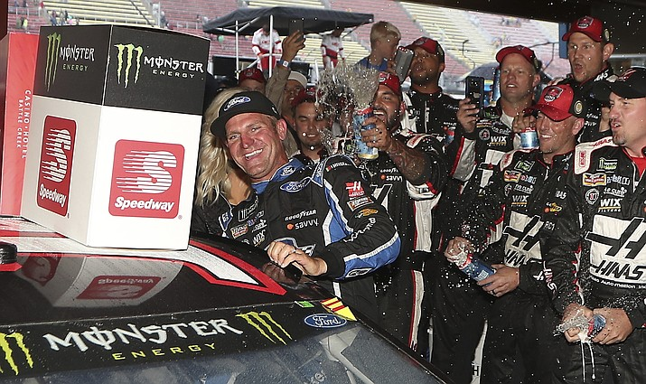 Clint Bowyer, left, is doused after winning a shortened NASCAR Cup Series auto race, Sunday, June 10, 2018, in Brooklyn, Mich. (AP Photo/Carlos Osorio)