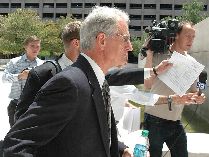 Former utility regulator Gary Pierce rushes past reporters last year following his initial court appearance. (Photo by Howard Fischer/Capitol Media Services)