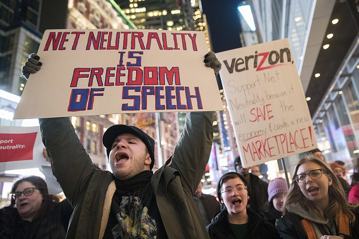In this Thursday, Dec. 7, 2017 file photo, Demonstrators rally in support of net neutrality outside a Verizon store in New York. Consumers aren't likely to see immediate changes following Monday, June 11, 2018 formal repeal of Obama-era internet rules that had ensured equal treatment for all. Rather, any changes are likely to happen slowly, and companies will try to make sure that consumers are on board with the moves, experts say. (AP Photo/Mary Altaffer, File)