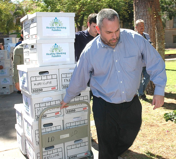 Elections Director Eric Spencer helps bring petitions to raise the minimum wage into state offices in 2016. It was voter approval of that measure that caused Republican lawmakers last year to make it more difficult to put future initiatives on the ballot. (Capitol Media Services file photo by Howard Fischer)
