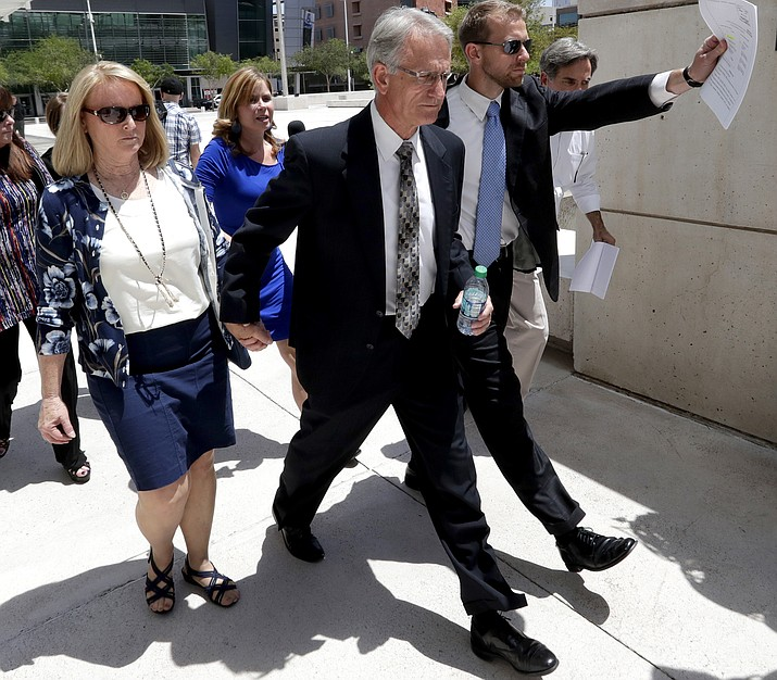 In this June 7, 2017, photo, Former Arizona utility regulator Gary Pierce, center, and his wife Sherry, left, leave Federal Court in Phoenix as their lawyer tries to shied them from cameras after being arraigned on bribery and fraud charges. Pierce who is charged with accepting bribes from a water company owner in exchange for favorable decisions. (Matt York/ AP, file)