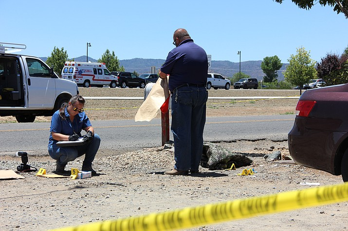 Evidence technicians with the Yavapai County Sheriff's Office document and bag a number of items left behind by a man shot along Frontage Road in Castle Canyon Mesa early Tuesday morning, June 12.