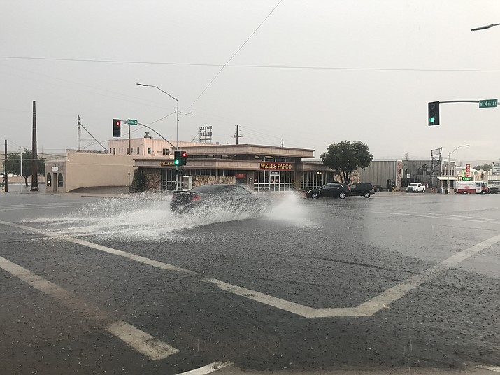 A car splashes through an intersection in downtown Kingman following a monsoon thunderstorm last year. The outlook is for a weaker-than-usual monsoon season this year, according to the National Weather Service. (Daily Miner File Photo)