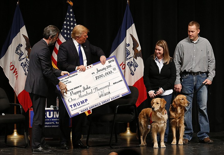 In this Jan. 30, 2016 file photo, Donald Trump, second from left, stages a check presentation with an enlarged copy of a $100,000 contribution from the Donald J. Trump Foundation to Puppy Jake, a veteran's charity, at a campaign event in Davenport, Iowa during Trump's run for president. New York Attorney General Barbara Underwood filed a lawsuit Thursday June 14, 2018, accusing Trump of illegally using his charitable foundation to pay legal settlements related to his golf clubs and to bolster his presidential campaign with Foundation disbursements such as this one in Iowa. (AP Photo/Paul Sancya, File)