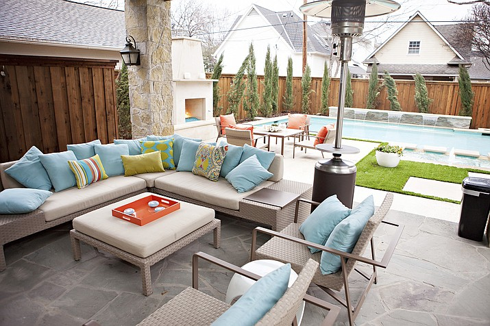 "Fans for hot days and space heaters for cold nights can help make a patio feel even more like an ""outdoor living room,"" as seen in this backyard sitting area designed by Abbe Fenimore. Designers say that outdoor furnishings have come a long way. Look for rugs, lighting, sofas and more.  (Melanie Johnson Photography/Abbe Fenimore via AP)"