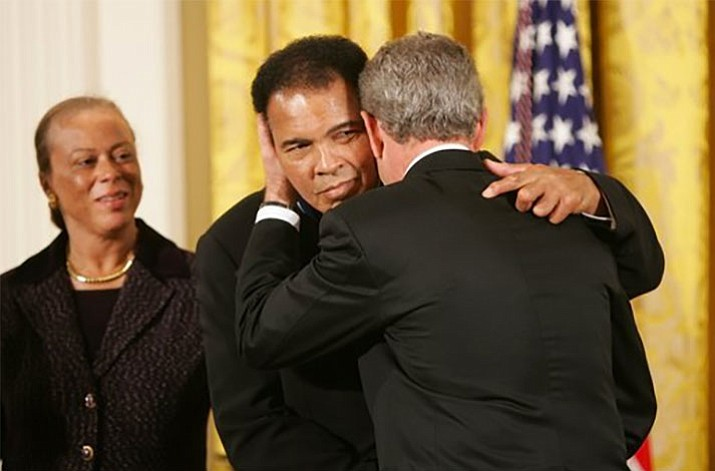 """In this Nov. 2005 file photo President George W. Bush embraces three-time heavyweight boxing champion of the world Muhammad Ali after presenting him with the Presidential Medal of Freedom during ceremonies at the White House. President Donald Trump said he is thinking """"very seriously"""" about pardoning Muhammad Ali, even though the Supreme Court vacated the boxing champion's conviction in 1971. (White House photo by Paul Morse)"""
