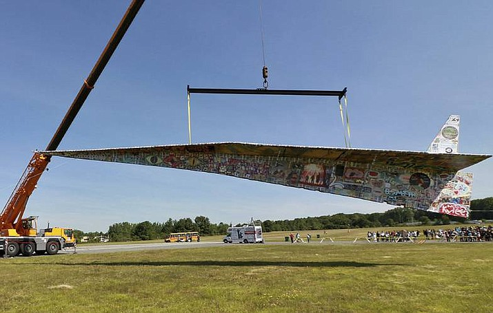 The Revolving Museum of Fitchburg's Project Soar paper airplane hangs from a crane at the Fitchburg Municipal Airport, Tuesday, in Fitchburg. The nearly one-ton plane, 4 feet longer than a bowling lane, is a contending entry into the Guinness World Record for World's Largest Paper Plane. (John Love/The Sentinel & Enterprise via AP)