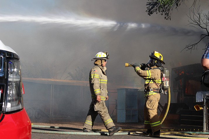 Northern Arizona Consolidated Fire District firefighters hose down the mobile home that was engulfed in flames on Snavely Avenue in May. Kingman Fire Department assisted during this fire. (Photo by Vanessa Espinoza/Daily Miner)