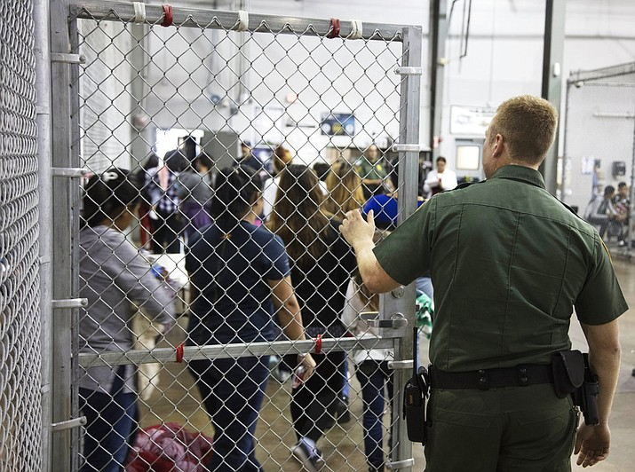 A U.S. Border Patrol agent watches as people who have been taken into custody related to cases of illegal entry into the United States, stand in line at a facility in McAllen, Texas, Sunday, June 17, 2018. (U.S. Customs and Border Protection's Rio Grande Valley Sector)
