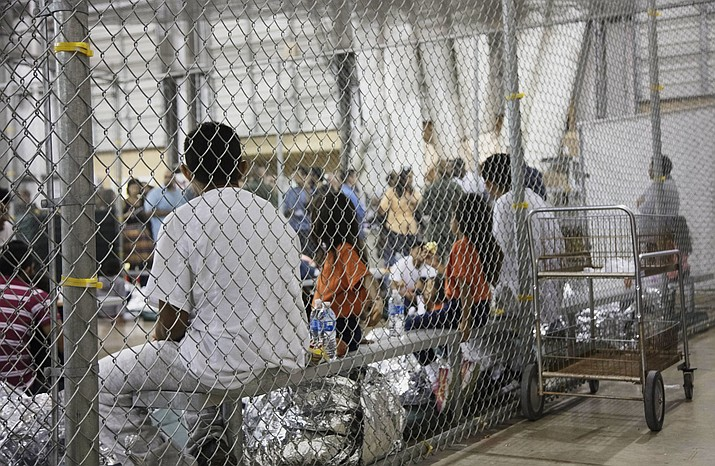 In this photo provided by U.S. Customs and Border Protection, people who've been taken into custody related to cases of illegal entry into the United States, sit in one of the cages at a facility in McAllen, Texas, on Sunday, June 17, 2018. (U.S. Customs and Border Protection's Rio Grande Valley Sector, via AP)