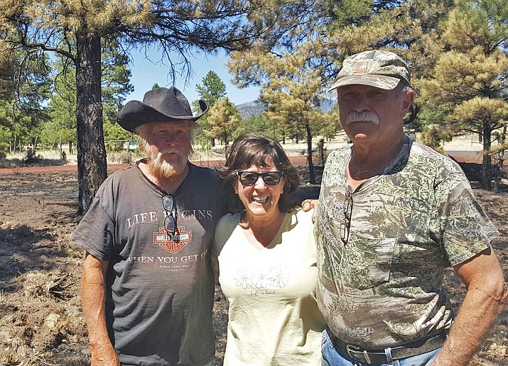 Bob Hausman, Sheri Williams and Val Williams stand at the site of a June 4 grass fire. The Williams credit Hausman for extinguishing the blaze with his backhoe and preventing its spread. (Submitted photo)