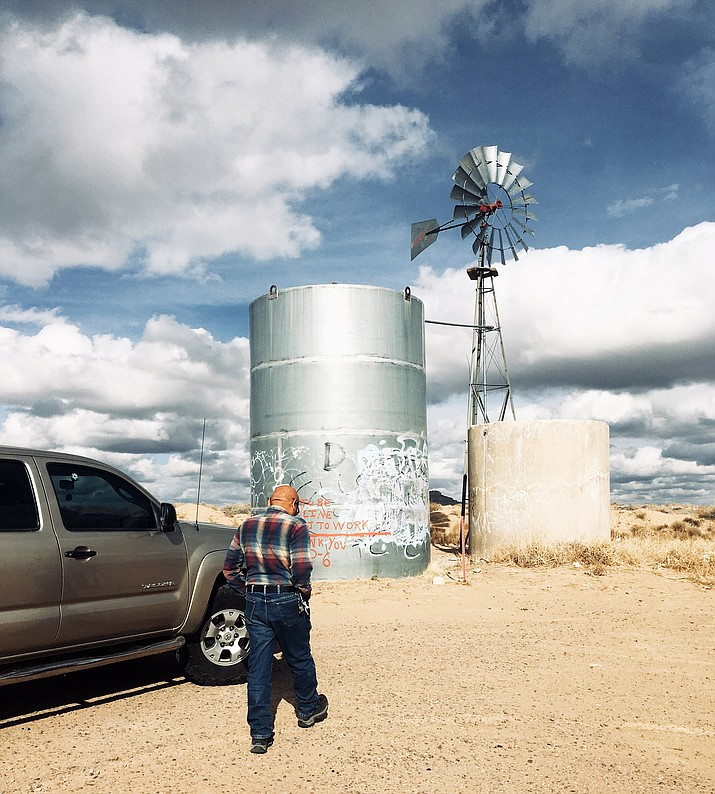Mervin Yoyetewa, who lives on First Mesa on the Hopi Reservation, approaches a windmill water pump, which is often empty. A growing concern for Yoyetewa and many Hopi families is the concentration of arsenic getting higher as water levels decline in the aquifer. (Rowan Lynam)