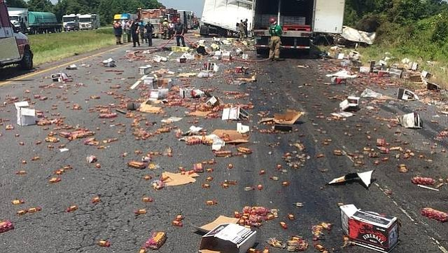 This photo provided by the The Arkansas Department of Transportation shows the aftermath of a wreck on Interstate 40 east of Little Rock on Thursday, June 14, 2018, that left hundreds of miniature bottles of whiskey on the roadway. Highway officials say two tractor-trailers collided and that the highway's westbound lanes were closed about three hours. In addition to the Fireball bottles, a truck also spilled some type of produce. (Highway Patrol Cpl. Jeremy Watkins Arkansas Department of Transportation via AP)