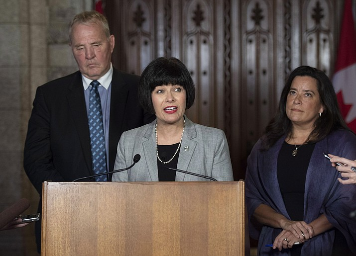 Minister of Health Ginette Petitpas Taylor, center, Minister of Justice and Attorney General of Canada Jody Wilson-Raybould, right, and Parliamentary Secretary to the Minister of Justice and Attorney General of Canada and to the Minister of Health Bill Blair, left, speak to reporters during a press conference on Bill C-45, the Cannabis Act, in the Foyer of the House of Commons on Parliament Hill in Ottawa, Ontario on Wednesday, June 20, 2018. The Canadian government said it will soon announce the date of when cannabis will become legal, but warns it will remain illegal until then. (Justin Tang/The Canadian Press via AP)