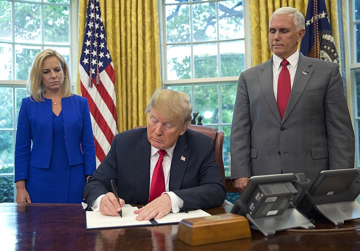 President Donald Trump signs an executive order to keep families together at the border, but says that the 'zero-tolerance' prosecution policy will continue, at an event in the Oval Office of the White House in Washington, Wednesday, June 20, 2018. Standing behind Trump are Homeland Security Secretary Kirstjen Nielsen, left, and Vice President Mike Pence. (AP Photo/Pablo Martinez Monsivais)