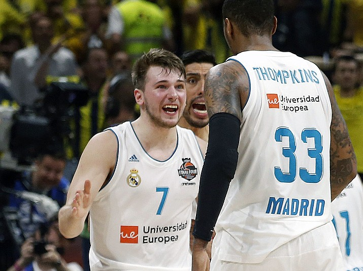 In this May 20, 2018, file photo, Real Madrid's Luka Doncic (7) reacts with teammate Trey Thompkins after winning their Final Four Euroleague final basketball match against Fenerbahce, in Belgrade, Serbia. The Slovenian guard heads the list of international players expected to be selected in the NBA draft. (Darko Vojinovic/AP, File)