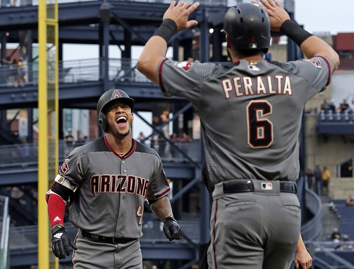 Arizona Diamondbacks' Ketel Marte (4) is greeted by David Peralta (6) as he crosses home plate after hitting two-run home run off Pittsburgh Pirates starting pitcher Chad Kuhl, left, in the first inning of a baseball game in Pittsburgh, Thursday, June 21, 2018. (Gene J. Puskar/AP)