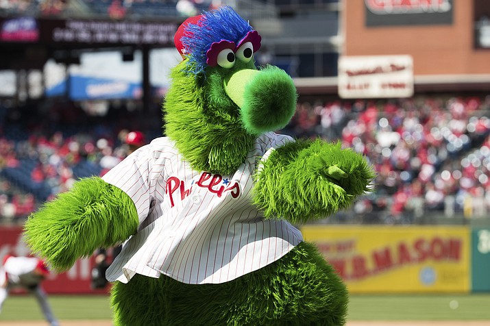 In this April 5, 2018 photo, the Phillie Phanatic reacts prior to the first inning of a baseball game against the Miami Marlins  in Philadelphia. Kathy McVay says she was at Monday, June 18, Phillies game when the team's mascot, the Phillie Phanatic, rolled out his hot dog launcher. McVay was sitting near home plate and all of a sudden she says a hot dog wrapped in duct tape struck her in the face. She left the game to get checked out at a hospital, and she says she has a small hematoma. (Chris Szagola/AP)