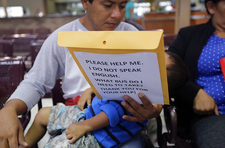 Immigrants from Guatemala seeking asylum look over travel packets as they wait at the bus station after they were processed and released by U.S. Customs and Border Protection, Thursday, June 21, 2018, in McAllen, Texas. President Donald Trump signed an executive order to end family separations at the border. (AP Photo/Eric Gay)