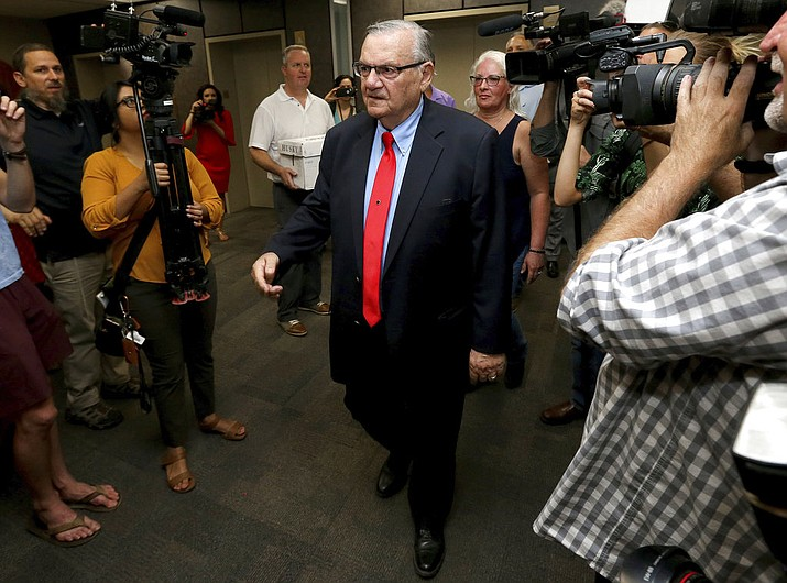 In this May 22, 2018, file photo, former Arizona Sheriff Joe Arpaio arrives at the Arizona Secretary of State's office in Phoenix, to turn in petition signatures in his bid to appear on the ballot in the race to succeed retiring U.S. Sen. Jeff Flake. Arpaio is seeking an investigation into his claim that the U.S. Justice Department meddled in his unsuccessful 2016 campaign for sheriff in metro Phoenix. Arpaio alleges the agency tried to sway voters against him by agreeing to prosecute a criminal case against him just weeks before the election. (AP Photo/Matt York, File)