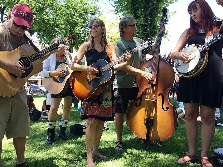 From left, Lem Johnson on guitar, Christina Davis on guitar, Jim Davis on the upright bass, and Chloey Davis on banjo play on the northern end of courthouse plaza Saturday, June 23. (Jason Wheeler/Courier)