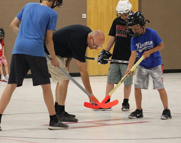 Lewis King, center, drops the puck during a recent floor hockey session. (Photo by Giancarlo Narvarte/For the Daily Miner)
