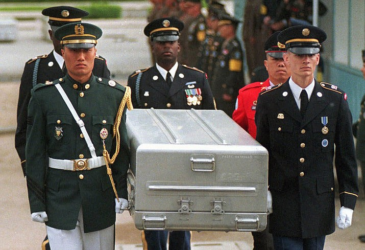 In this May 14, 1999, file photo, U.N. honor guards carry a coffin containing the remains of the American soldiers after it was returned from North Korea at the border village of Panmunjom, South Korea. South Korean media reported that the U.S. military plans to send 215 caskets to North Korea through a border village on Saturday, June 23, 2018, so that the North could begin the process of returning the remains of U.S. soldiers who have been missing since the 1950-53 Korean War. (AP Photo/Ahn Young-joon, File)