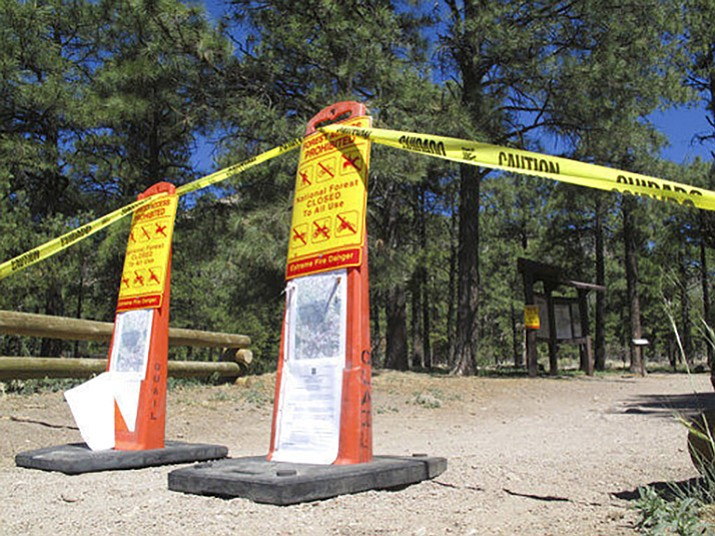 In this May 24, 2018 file photo signs are posted at trails leading into the national forest in Flagstaff, Ariz., telling the public no one is allowed in. Multiple areas of national forests around Arizona are closed because of extreme fire danger. The partial closures in a handful of Arizona's national forests represent a small percentage of the land overall. But they're putting a damper on camping, hiking, fishing and mountain biking in popular recreation areas. (AP Photo/Felicia Fonseca)
