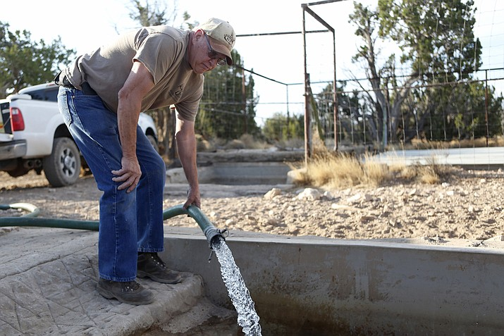 Mike Anderson of the Arizona Elks Society fills a wildlife water tank off a forest road near Flagstaff.  (Ben Shanahan/Arizona Daily Sun via AP)