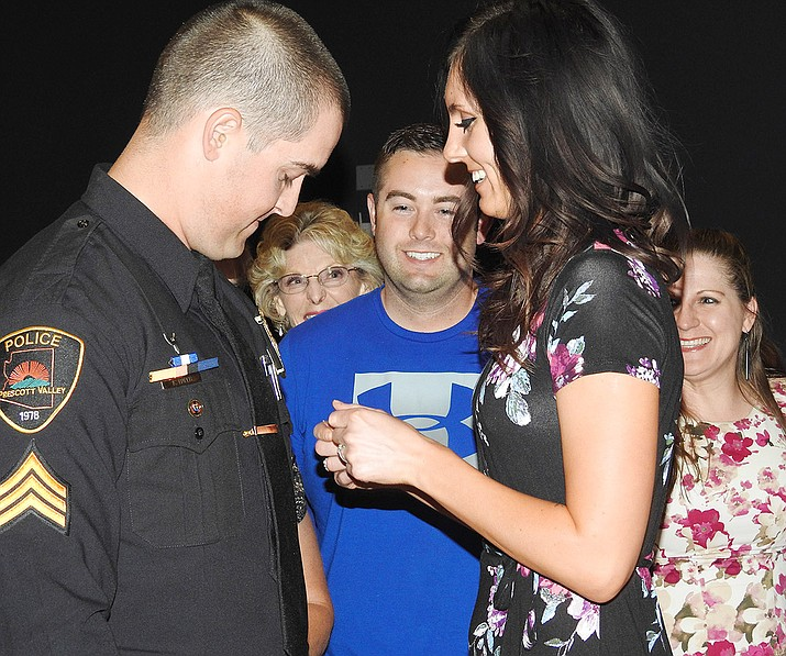Newly promoted PVPD sergeant Kyle Hader's fiancee, Meagan, pins the badge on his uniform with family members looking on after being sworn in at the June 14 Town Council meeting. (Town of Prescott Valley/Courtesy)