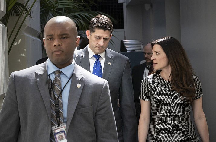 Speaker of the House Paul Ryan, R-Wis., confers with his press secretary AshLee Strong, right, as a member of his protection detail escorts at left, following a closed-door GOP strategy session at the Capitol in Washington, Tuesday, June 26, 2018. (J. Scott Applewhite/AP Photo)