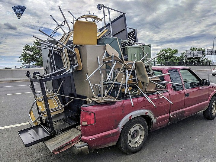 This June 20, 2018 photo released by the Massachusetts State Police shows an overloaded truck pulled over for uncovered cargo on Interstate 91 in Springfield, Mass. The same unnamed driver was pulled over in by police in Chicopee, Mass., on June 25 for another unsecured load. (Massachusetts State Police via AP)