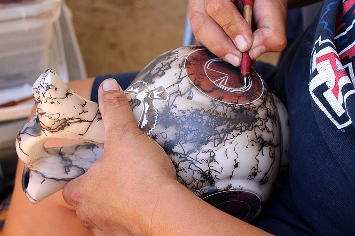 Eric Greenstone, the owner of Greenstone Collection, is hand carving a piece of pottery at the arts and crafts fair June 2. (Photo by Vanessa Espinoza/Daily Miner)