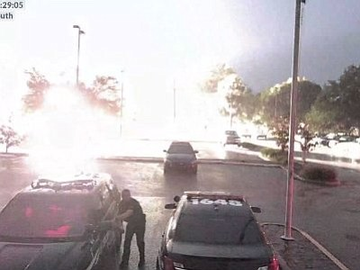 A Florida police officer loading up his vehicle got quite a shock when lightning struck in the parking lot behind him. Surveillance video released by the Apopka Police Department shows the bolt lighting up the parking lot Tuesday evening. (June 28)
