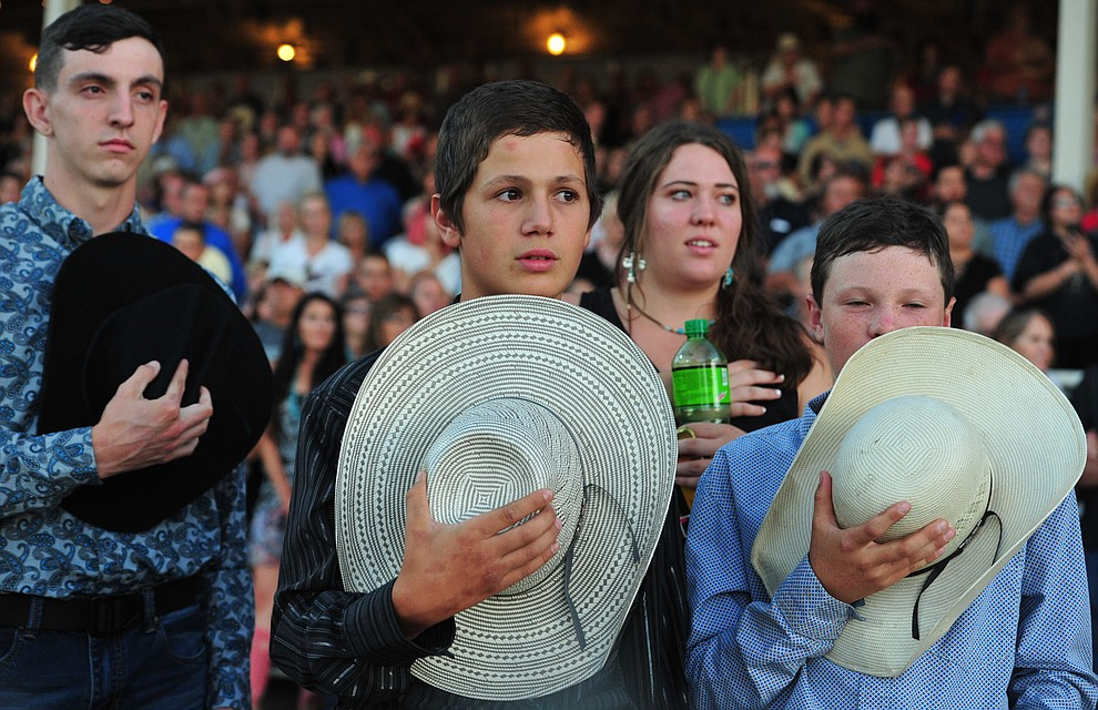 Three boys remove their hats for the National Anthem during the opening performance of the Prescott Frontier Days Rodeo Thursday, June 28, 2018. (Les Stukenberg/Courier)