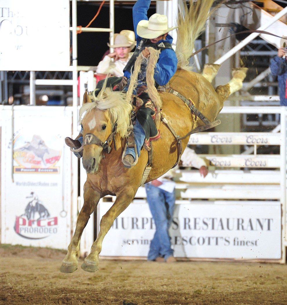 Tyler Baeza rides Sun Pop for a score of 78 in the saddle bronc during the opening performance of the Prescott Frontier Days Rodeo Thursday, June 28, 2018. (Les Stukenberg/Courier)