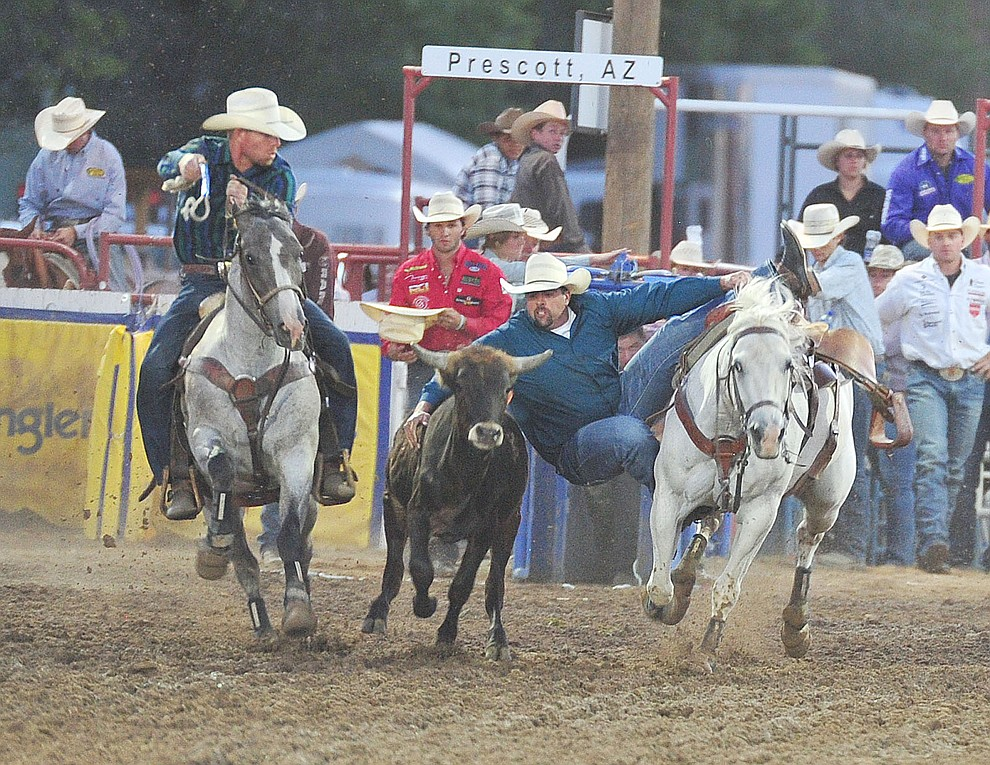 Gary Gilbert drops down during the steer wrestling in the second performance of the Prescott Frontier Days Rodeo Friday, June 29, 2018.(Les Stukenberg/Courier)