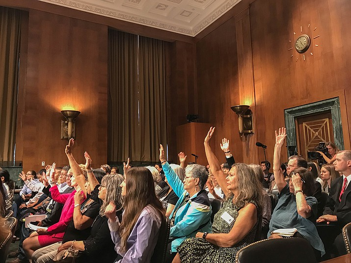 "Audience members at a Senate hearing on a bill to compensate ""downwinders"" – people affected by radiation from nuclear testing – raise their hands when asked if they are downwinders. (Photo by Bryan Pietsch/Cronkite News)"