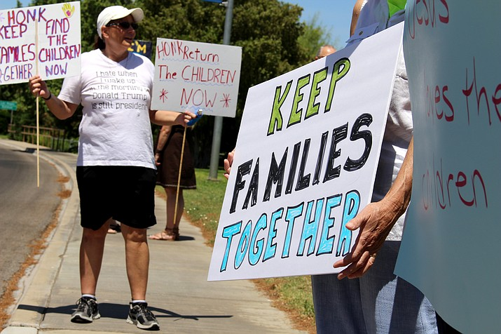 Supporters for Keeping Families Together at the U.S.-Mexico border held up their signs along Route 66 at Locomotive Park while cars passed by honking in support. (Photo by Vanessa Espinoza/Daily Miner)