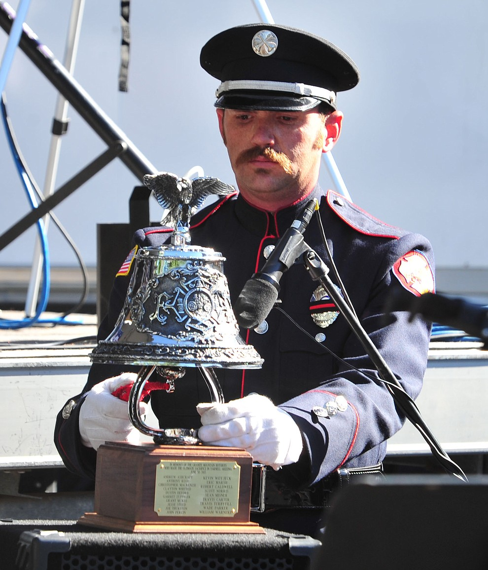 Prescott firefighter Adam Morris rings the bell after each name is read during a Remembrance Ceremony for the 19 Granite Mountain Hotshots Saturday, June 30, 2018.(Les Stukenberg/Courier)