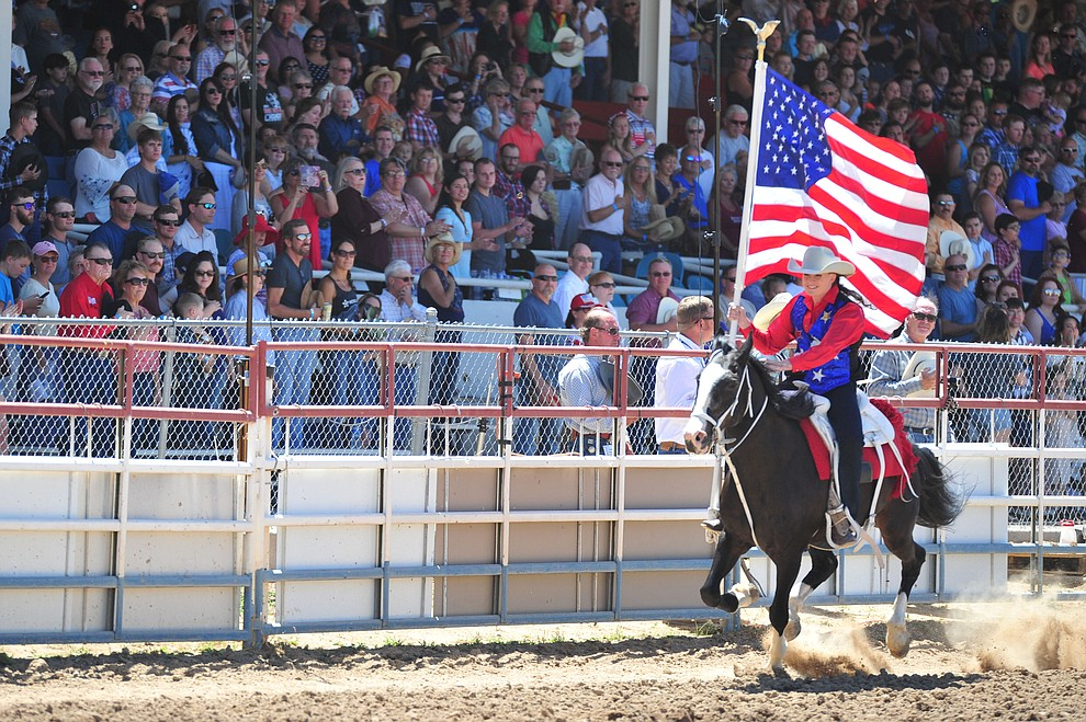 Sami Kilduff brings in the American Flag during third performance of the Prescott Frontier Days Rodeo Saturday, June 30, 2018.(Les Stukenberg/Courier)