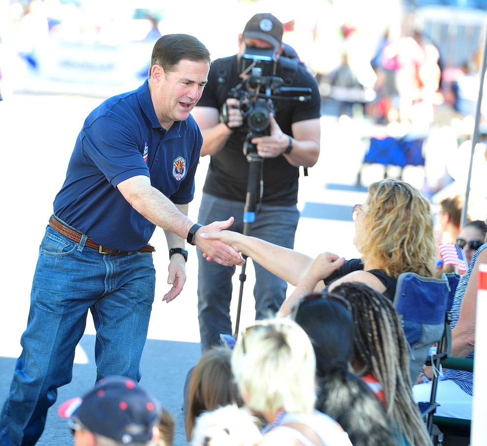 Governor Doug Ducey preshes the flesh during the annual Prescott Frontier Days Parade through the downtown Prescott area Saturday, June 30, 2018.(Les Stukenberg/Courier)
