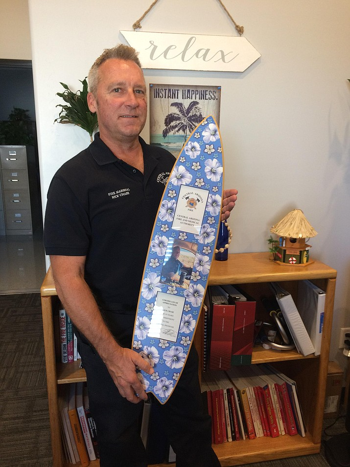 Central Arizona Fire and Medical Authority Fire Marshal Rick Chase with his surf board award honoring him for 18 years with the Fire Pal program. The certificate was presented to him at an authority board meeting on Monday, June 25. (Nanci Hutson/Courier)