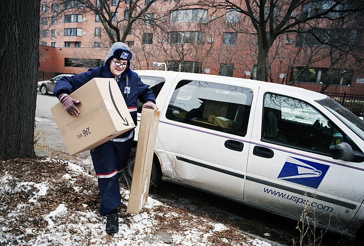 In this Dec. 24, 2017, file photo, United States Postal Service worker Missie Kittok, who has been a letter carrier for 15 months, helps deliver some packages in time for Christmas in Minneapolis. Amazon's Prime shipping program is forcing other companies to radically think of new initiatives to get products to shoppers' doors faster. (Richard Tsong-Taatarii/Star Tribune via AP, File)