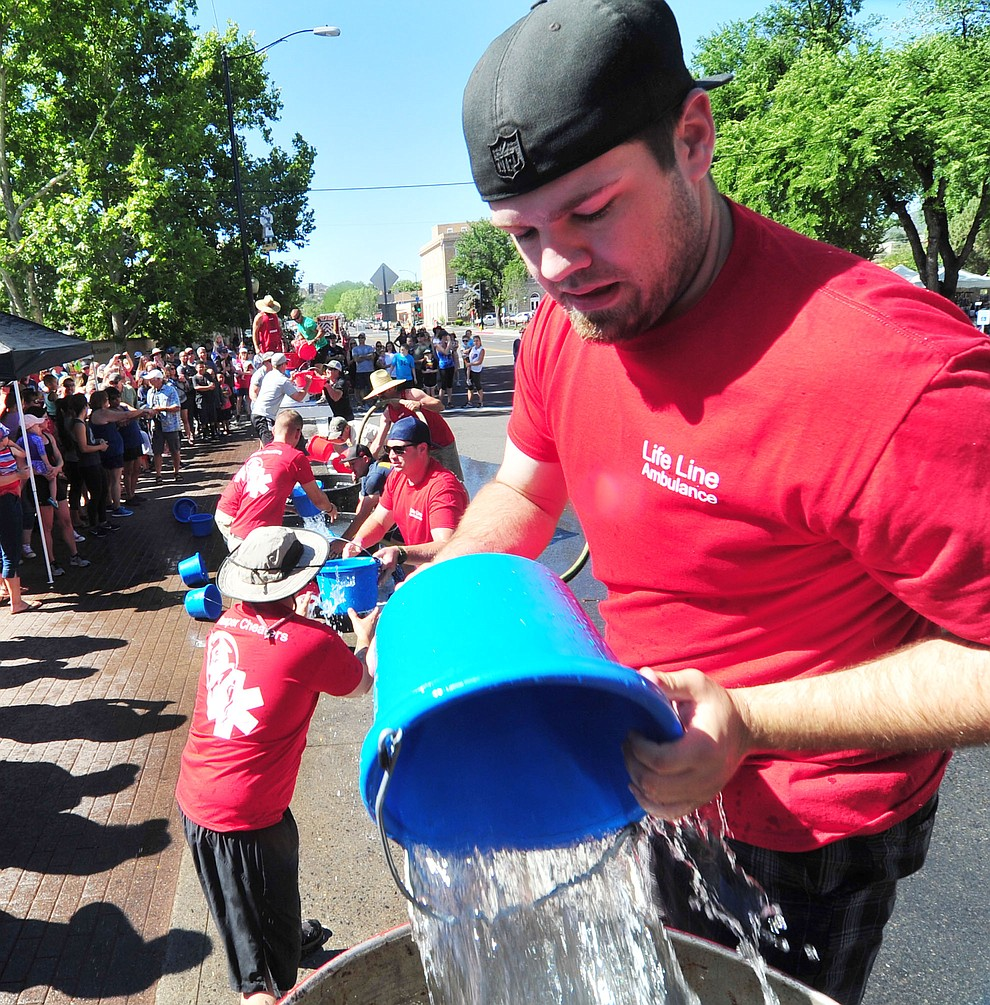 A Lifeline Ambulance team competes in the bucket brigade during the annual Hose Cart Races and Bucket Brigade held in downtown Prescott Sunday July 1, 2018. The annual event recreates actual competitions held by early Prescott fire companies from the late 1880's like the Tough's Hose Company Number 1, the Dudes Hose Company Number 2, the Mechanics Hook and Ladder Company Number 1 and the O.K Hose Company Number 3. (Les Stukenberg/Courier)