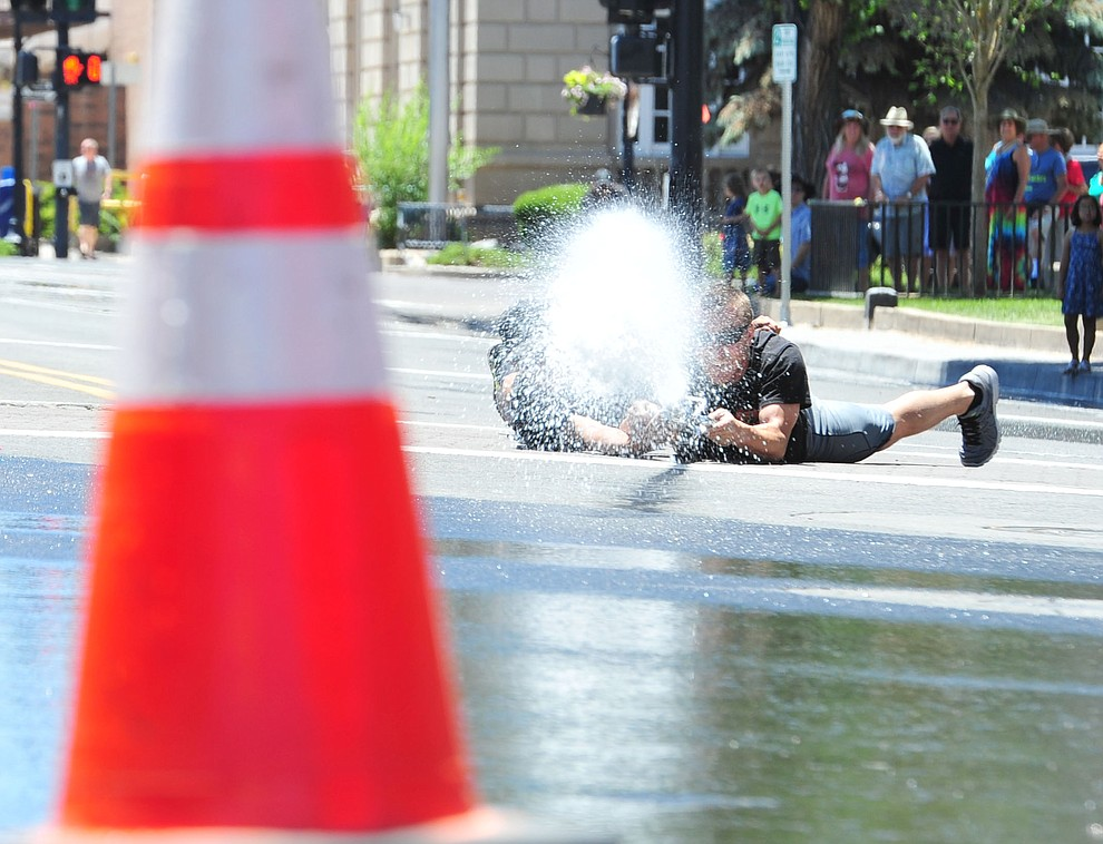 Prescott National Forest Engine 930 takes aim for the win during the annual Hose Cart Races and Bucket Brigade held in downtown Prescott Sunday July 1, 2018. The annual event recreates actual competitions held by early Prescott fire companies from the late 1880's like the Tough's Hose Company Number 1, the Dudes Hose Company Number 2, the Mechanics Hook and Ladder Company Number 1 and the O.K Hose Company Number 3. (Les Stukenberg/Courier)